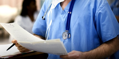 Doctor holding medical records in hospital, portrait