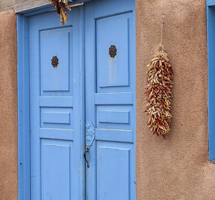 Blue doors of an old adobe house in Taos, New Mexico. Hanging peppers and indian corn.